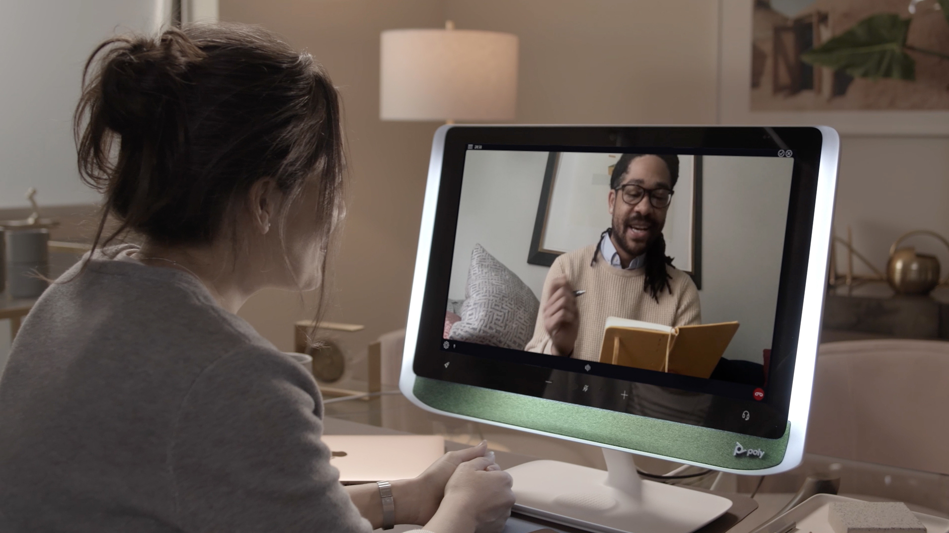 Woman in a virtual meeting with a man reading from a book