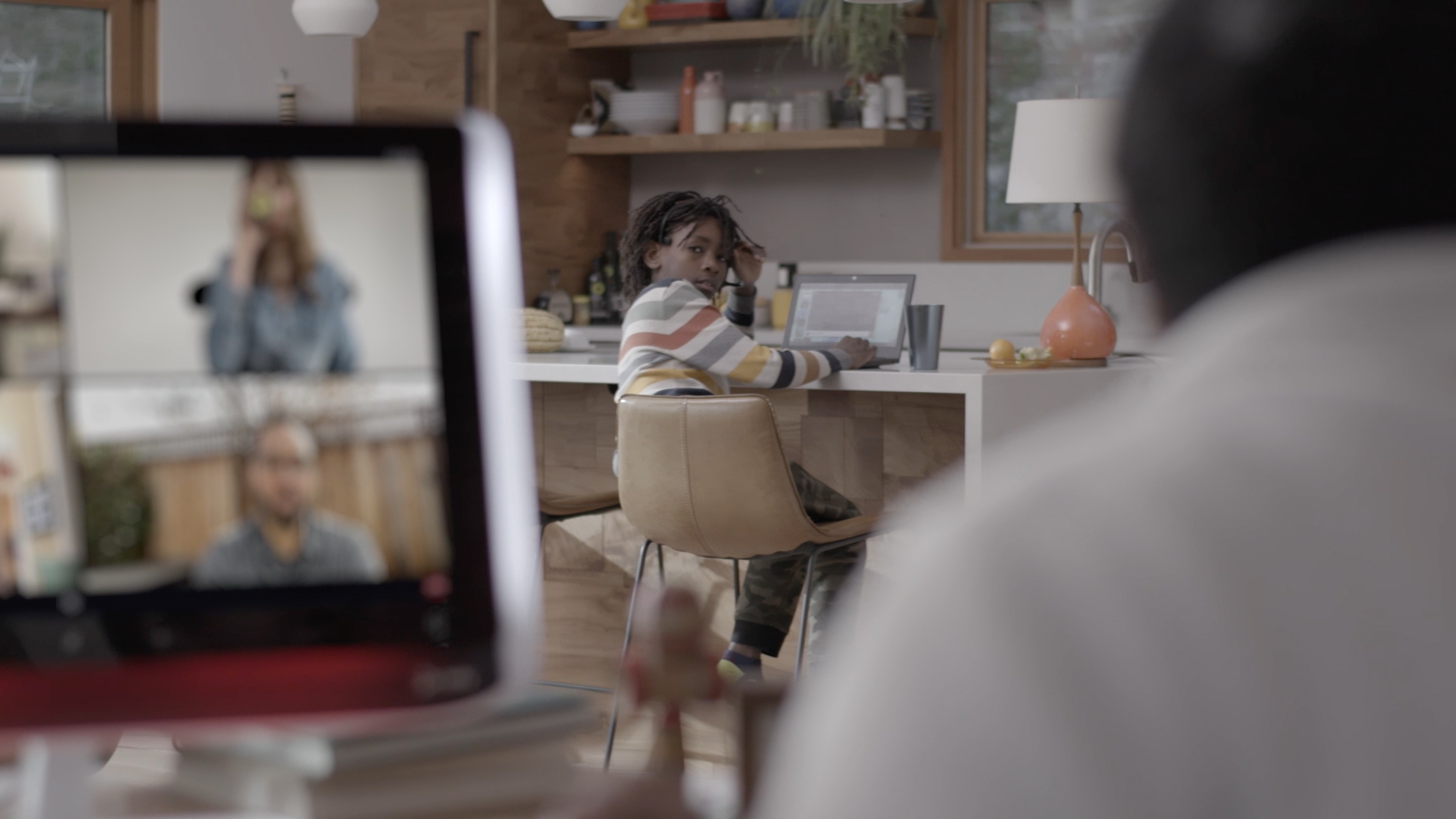 Virtual meeting with child in the background on a laptop computer