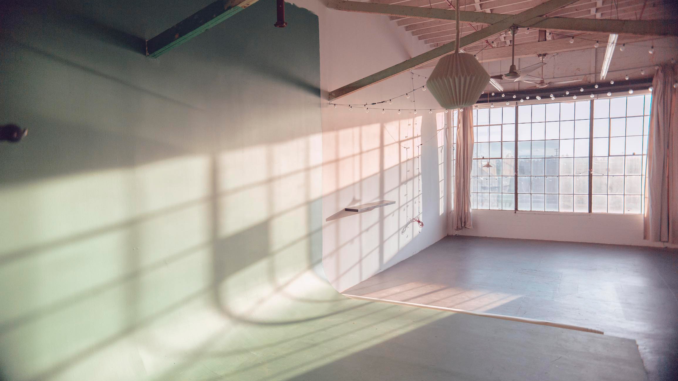 empty studio with cyc wall and window with natural light